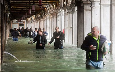 Turistas sob arcos inundados da Praça St Mark durante um período de alta-água (Acqua Alta) em Veneza. As inundações, causadas por uma convergência de marés altas e um forte vento Sirocco, atingiu cerca de 150 centímetros.