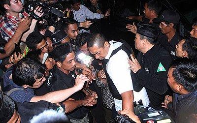 A polícia Indonésia tentar proteger Siti Aisyah (C), que estava em julgamento na Malásia pelo  assassinato de Kim Jong nam, meio-irmão do líder norte-coreano Kim Jong-Un, no momento em que ela chega à sua cidade após ter a acusação retirada.
