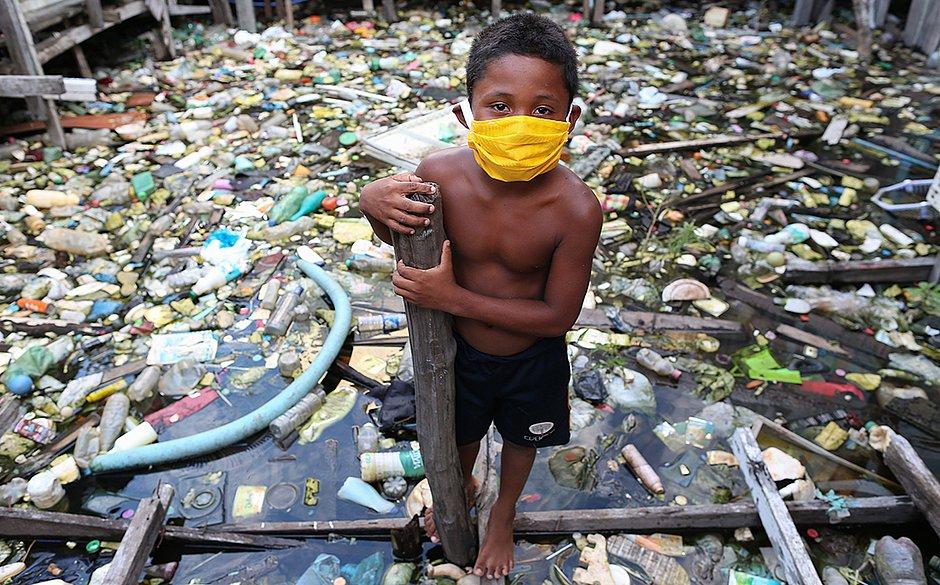 Um garoto da comunidade ribeirinha de Educandos usa uma máscara facial durante a pandemia de coronavírus COVID-19 em Manaus.