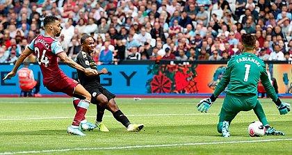 Sterling coloca a bola entre as pernas do goleiro Fabianski ao marcar o terceiro gol do City