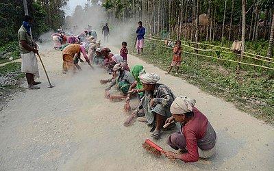 Operários indianos trabalham na construção de estradas em Panbari no distrito de Kokrajhar, cerca de 191km de Guwahati no nordeste do estado de Assam.