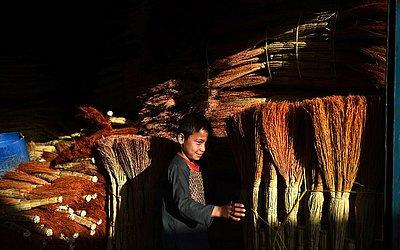 Garoto afegão vende vassouras em Mazar-i-Sharif.