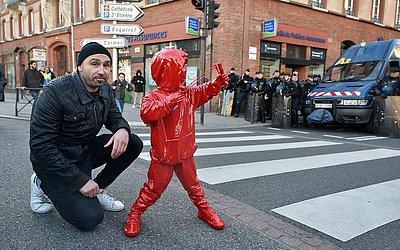 O artista James Colomina posa ao lado de sua escultura em frente à polícia de choque em Toulouse, no sul da França, durante uma manifestação de estudantes e professores contra reformas no sistema de ensino francês.