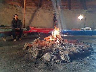 O guia Ezequiel Epulef, 26 anos, e a fogueira acessa na ruca: fumaça que 'purifica' visitante