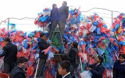 Crianças e voluntários do Nepal amarram sacos de plástico reciclados para fazer uma escultura representando o mar morto em uma tentativa de definir um novo recorde mundial para a maior escultura feita de sacos de plástico em Kathmandu.