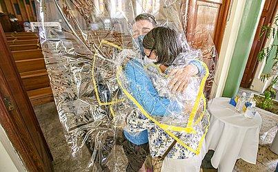 A cortina que permitiu os abraços é feita de plástico e foi higienizada após cada abraço com a aplicação de álcool em gel.