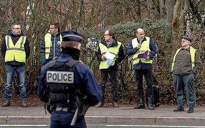 Agentes da polícia francesas vigim um grupo de manifestantes do colete amarelo em frente ao centro de imposto em Amiens, norte da França, durante uma visita do ministro de ações públicas e gestão de contas.
