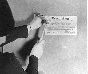 Funcionária de saúde de Minneapolis, Estados Unidos, postando cartaz de quarentena para doentes de escarlatina em 1907
