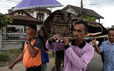Parentes e rezadeiras carregam o corpo do policial muçulmano morto por supostos participantes de uma seita de fanáticos.