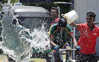 Espectador joga água num ciclista durante as celebrações do ano novo em Colombo, no Sri Lanka.