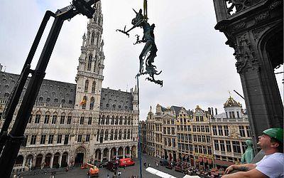 A estátua do dragão que faz parte do cata-vento de São Miguel Arcanjo no topo da Prefeitura de Bruxelas desde 1993, é içada por um guindaste e será levada para um Museu local.