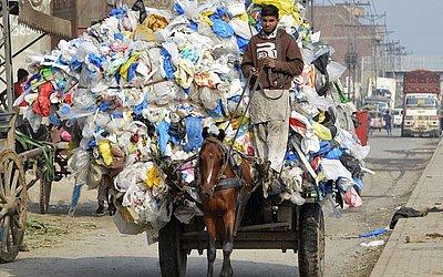 Um garoto paquistanês carrega resíduos de sacos de plástico em um carrinho à cavalo em Lahore.