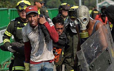 Um manifestante é socorrido na Ponte Internacional Simon Bolivar em Cúcuta, Colômbia, após ser ferido durante confrontos com as forças de segurança venezuelanas na fronteira de San Antonio del Táchira, na Venezuela.