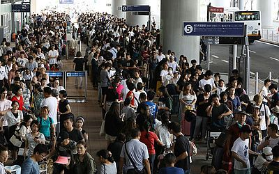 Passageiros presos durante a noite no Aeroporto Internacional de Kansai devido ao tufão Joebi esperam pelo ônibus que irá transportá-los ao aeroporto da cidade de Izumisano.