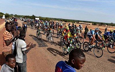 Ciclistas passam perto da aldeia de Yako, na fase 5 do tour de ciclismo do Burkina Faso.