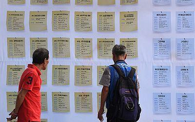 Desempregados conferem os anúncios de postos de trabalho numa feira de empregos em  Seul.