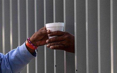 Uma xícara de chocolate quente passa através da cerca de um abrigo em Tijuana, México, na fronteira com os Estados Unidos para onde se desloca a grande caravana de migrantes da América Central.