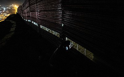 Um migrante centro-americano observa por uma brecha do muro na fronteira EUA-México de Tijuana para San Diego.
