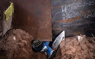 Migrante tenta atravessar o muro da fronteira entre Méxic/EUA através de um buraco no chão de  Playas de Tijuana.