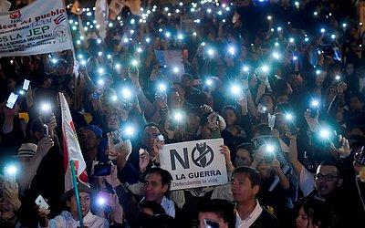 """Manifestantes protestam contra a reforma proposta pelo governo de uma Jurisdiç]ão Especial para a Paz (JEP) com uma placa dizendo """"não à guerra"""" em Bogotá, Colômbia."""
