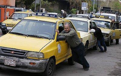 Motoristas de táxi empurram seus carros que ficaram sem gasolina para um posto na capital Síria, Damasco, que sofre com a escassez de combustível.