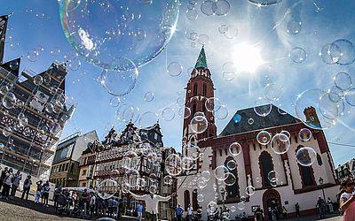 Artista de rua faz bolhas de sabão, em frente à igreja Alte Nikolaikirche na Praça Roemerberg em Frankfurt am Main, Alemanha Ocidental.