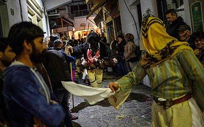Homens e mulheres vestidas em trajes de 'velho ' e ' Corela ' participam do Carnaval de Skyrian, na ilha de Esquiro, nordeste de Atenas