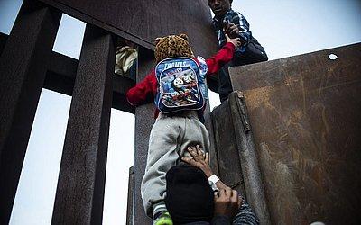 Garoto é ajudado a pular o muro que separa o México dos Estados Unidos, em Playas de Tijuana.