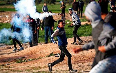 Manifestante palestino apara uma bomba de gás lacrimogêneo disparada pelas forças israelenses durante confrontos perto da fronteira com Israel a leste da cidade de Gaza.