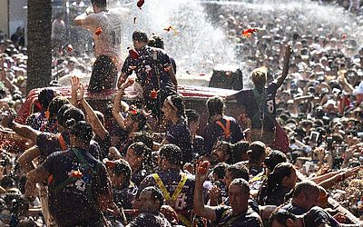 """Festival """"Tomatina"""" em Bunol. A festa anual que ocorre na última quarta-feira de agosto e celebra a sua 73ª edição é reconhecida como a """" maior guerra de comida do mundo""""."""