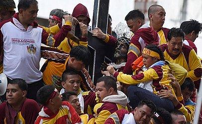 Católicos empurram-se uns aos outros ao tentar tocar a estátua do Nazareno Negro em uma  procissão em Manila.