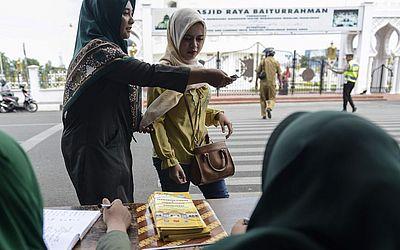 Polícia religiosa de Banda Aceh, na Indonésia, verifica a identidade de uma mulher que foi detida por usar calças apertadas.
