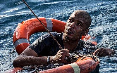 Um migrante é resgatado em 4 de janeiro de 2019 com boias e uma corda, depois que ele mergulhou no mar Mediterrâneo na costa de Malta do navio holandês Sea Watch3, em uma tentativa de alcançar a costa a nado.
