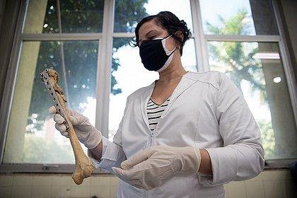 A perita médica legista Letícia Sobrinho com um osso na mão