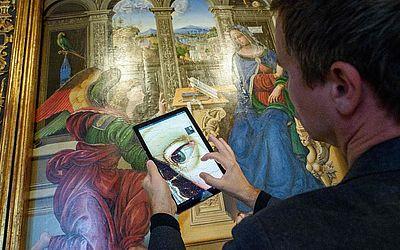 """Um homem observa pelo tablet os detalhes do quadro """"Verkündigung an Maria"""" no Museu Bode, em Berlim, onde os museus do estado se uniram ao Google para tornar acessíveis suas coleções a um público mais amplo."""