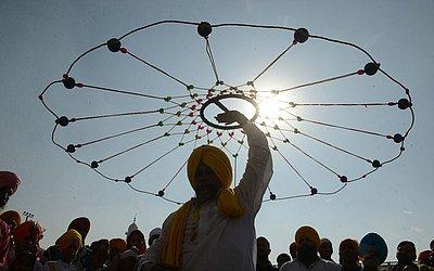 """Um jovem indiano Sikh demonstra suas habilidades de artes marciais """"gatka"""" durante uma procissão na véspera do 549th aniversário de nascimento de Guru Nanak Dev no Templo Dourado em Amritsar."""