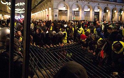 Os manifestantes de colete amarelo (Gilets jaunes) empurram as grades do Jardim das Tulherias ao lado da rua de Rivoli, no centro de Paris, durante uma manifestação contra o aumento dos preços do petróleo e do custo de vida.