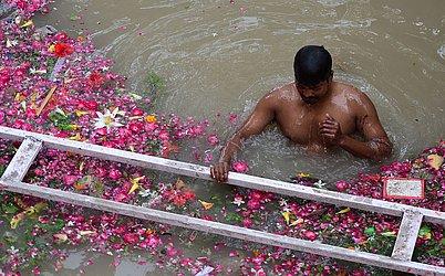 Devoto indiano mergulha em frente ao Templo de Hanuman Bade, na área de Senna depois que os níveis da água do rio Yamuna subiram após as inundações.