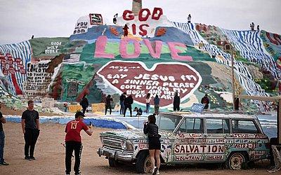 Turistas visitam a montanha da salvação, numa encosta coberta com mensagens bíblicas e símbolos construídos ao longo de um período de trinta anos pelo artista Leonard Knight, na cidade de laje, Califórnia.