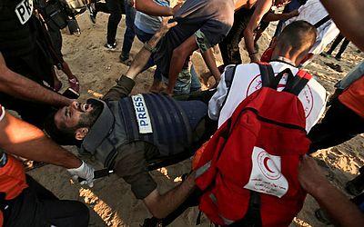 O cinegrafista palestino Atia Hijazi é levado para a ambulância após ser baleado na praia perto da fronteira com Israel, no norte da faixa de Gaza, durante uma manifestação contra o bloqueio israelense.