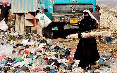 Uma mulher iraquiana carrega itens vendáveis de um aterro nos arredores da cidade sagrada iraquiana de Najaf.
