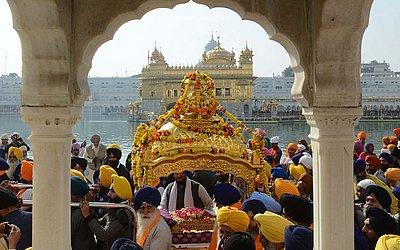 Devotos Sikh carregam o o Guru Granth Sahib, durante uma procissão na véspera do 549th aniversário de nascimento de Guru Nanak Dev no Templo Dourado em Amritsar.