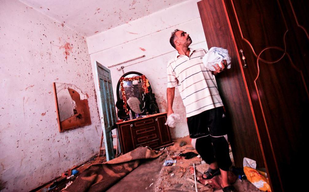 Um parente inspeciona a casa onde Khammash Enas palestina de 23 anos, grávida, foi morta com sua filha de 18 meses, durante um ataque aéreo israelense, em Deir Al-Balah, na faixa de Gaza.