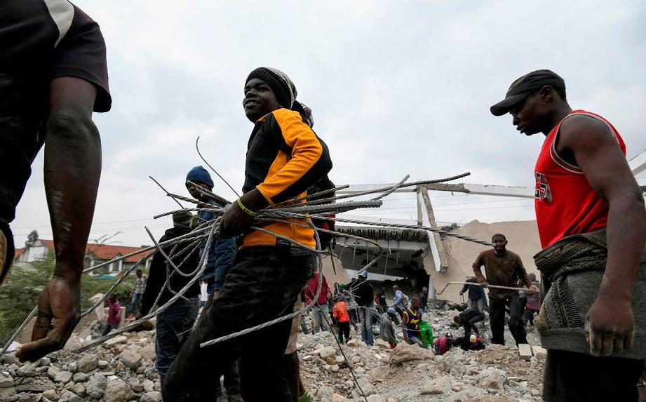 Sucateiros carregam fios e peças de metal do shopping demolido South Mall, em Nairobi. O estabelecimento é um dos inúmeros que foram demolidos por serem construídos ilegalmente em terras ribeirinhas.
