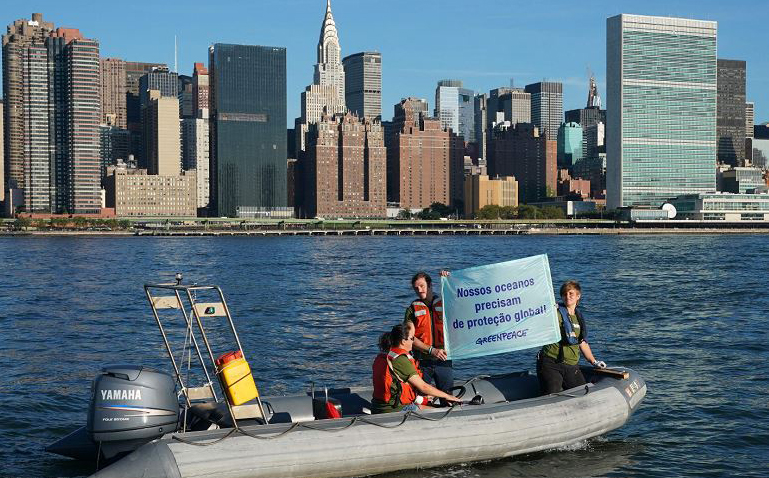 Ativistas do Greenpeace estendem um banner perto das Nações Unidas, para chamar a atenção para a campanha de santuários do  oceano. No East River em Nova York.