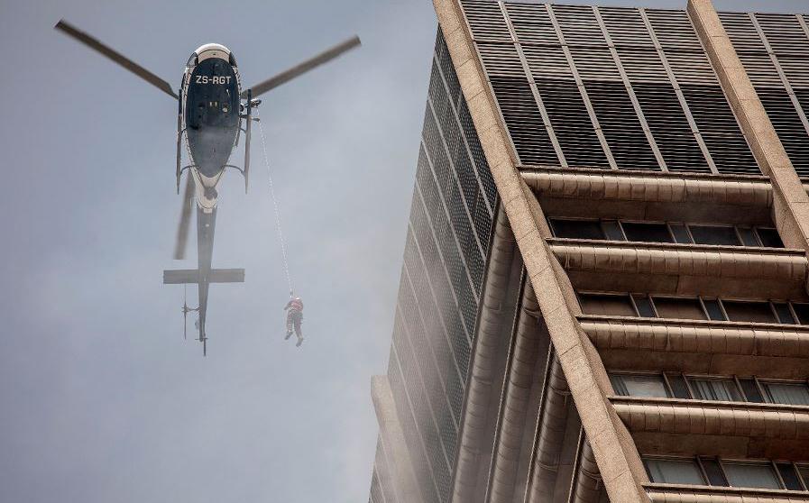 Um helicóptero da polícia sul africana resgata um bombeiro preso em um prédio em chamas no distrito central de negócios de Joanesburgo.