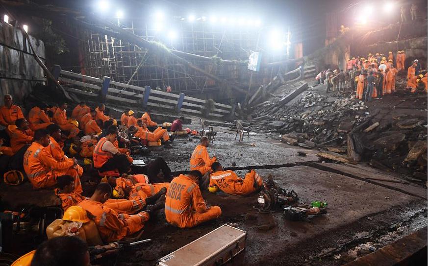 Trabalhadores de resgate indiano na operação de operação de busca e salvamento, depois que um segmento da ponte de Majerhat caiu em Calcutá, no estado indiano de Bengala Ocidental.