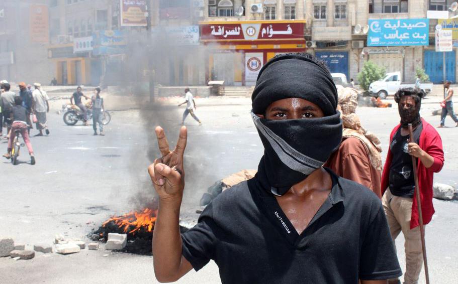 Manifestante iemenita bloquea uma estrada, em meio a protestos contra a inflação e o aumento do custo de vida na cidade de Áden.