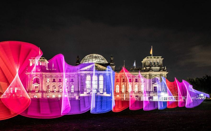 Padrões de luz colorida desenhados em frente ao edifício do Reichstag, sede do Parlamento alemão em Bundestag, Berlim.