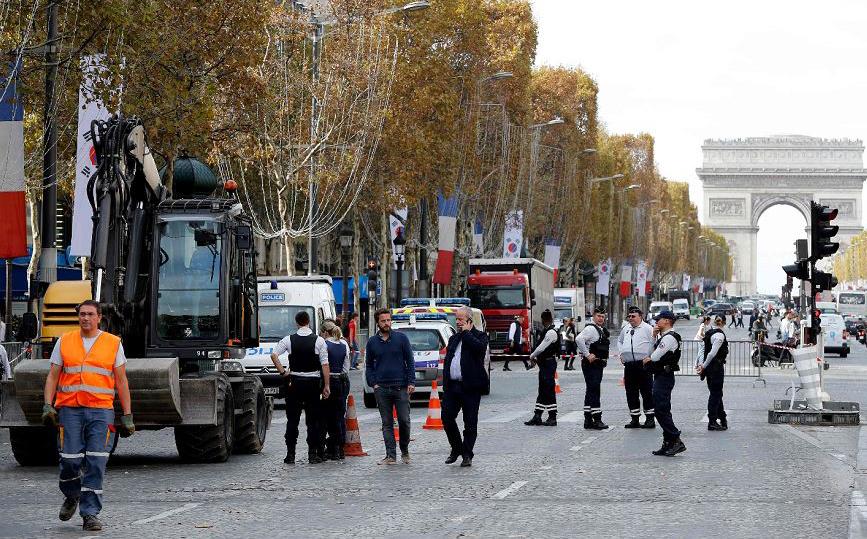 """Policiais vistoriam uma escavadeira que esmagou uma menina de 5 anos na avenida Champs-Elysées em Paris. De acordo com a investigação, """"Uma menina de 5 anos morreu e a mãe dela está gravemente ferida""""."""